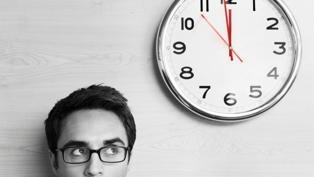 Man looking nervously at a clock striking 12 o'clock