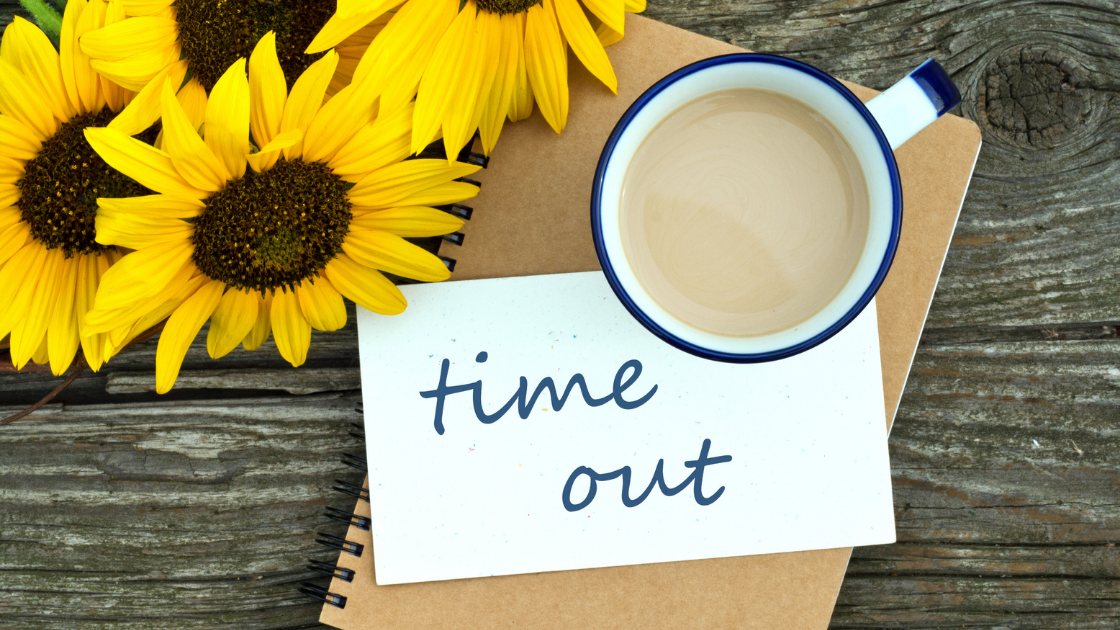 Image featuring sunflowers, a brown notepad, a mug of tea and note reading 'Time Out' on a table