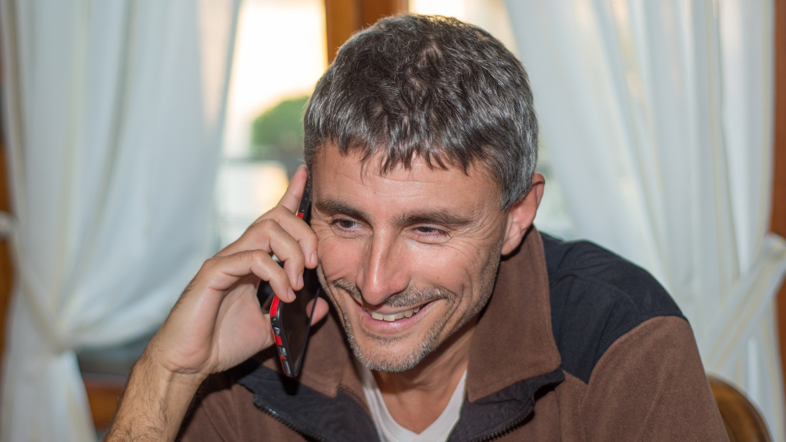 Man smiling whilst talking on the phone